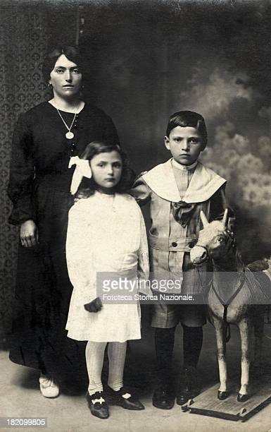 Young mother with her two children the little girl wears a summer white dress the boy wears the classic sailor suit near them there is a little horse...