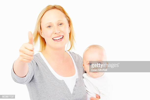 Young mother with thumb up holding baby on white background