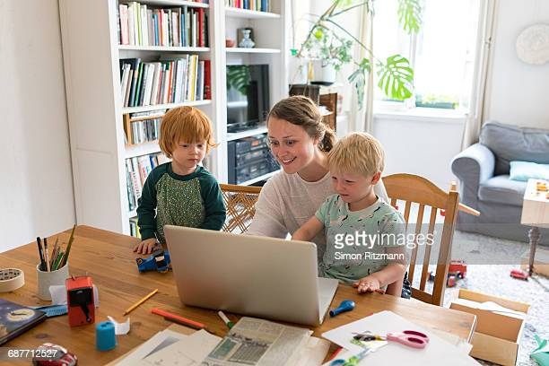 Young mother with two toddler sons in home office