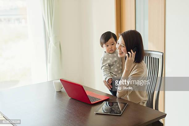 Young mother working with her baby girl at home
