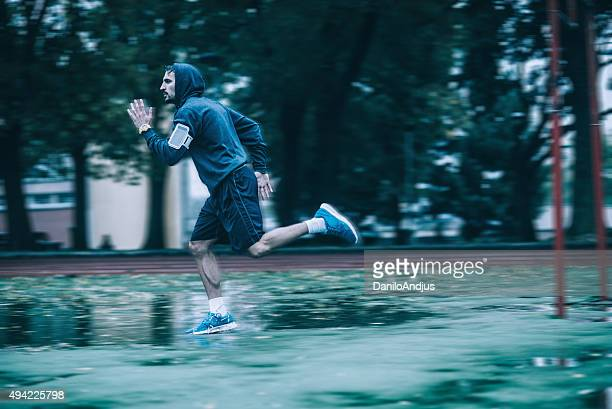 young motivated man running in the rain