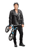 Full length portrait of a young motorcyclist holding a small childish bicycle and looking at the camera isolated on white background