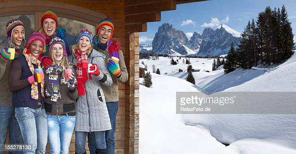 Young multi-ethnic people celebrating under cabin roof in snowy mountains
