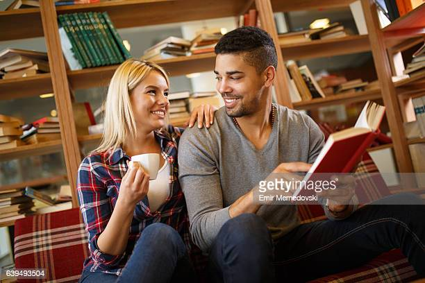 Young Multi-ethnic student couple enjoy reading book in the library.