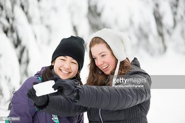Young Multi-Ethnic Women Girlfriends Taking Selfie in Winter Forest