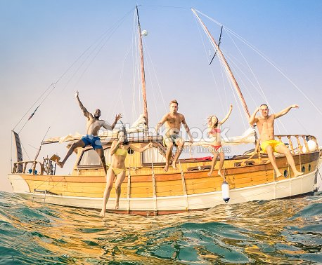 Young multiracial happy friends jumping from sailing party boat : Foto stock