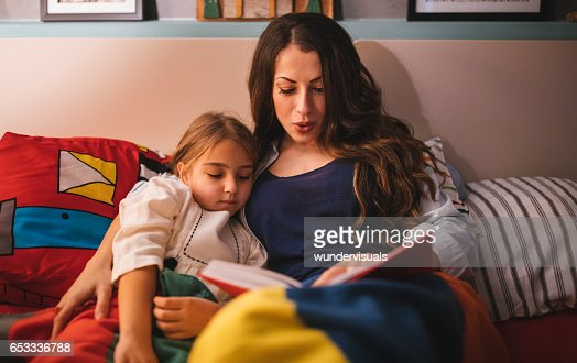 Young mum reading a story to her daughter in bed : Stock Photo
