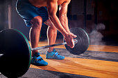 Young sporty man with naked torso clapping hands with chalk powder, preparing for weightlifting training. gym, power lifting equipment. Sports, fitness - healthy lifestyle concept.