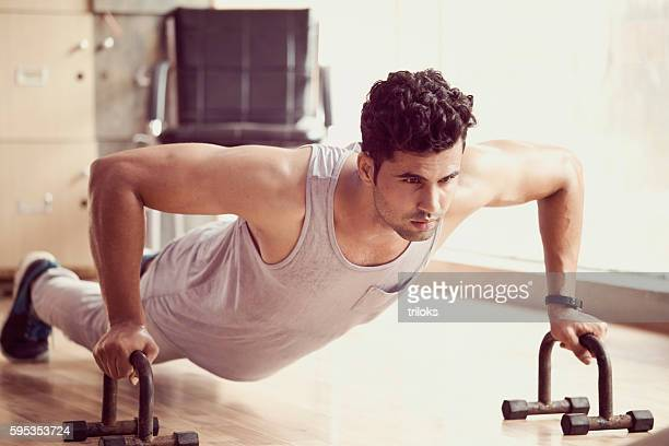Young muscular man doing push-ups in a gym