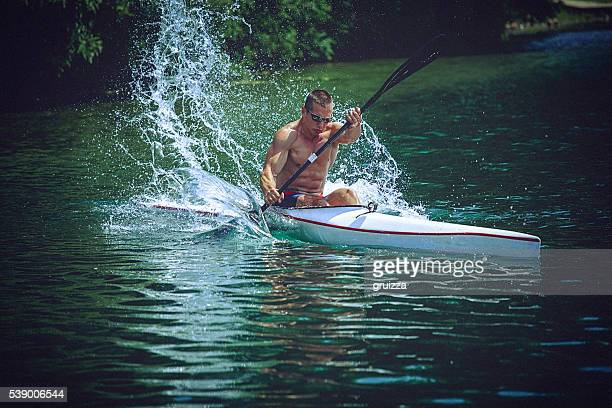 Young muscular man during kayak sprint training on still water.
