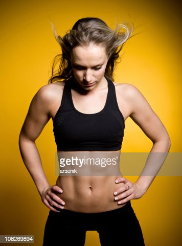 Young Muscular Woman in Exercise Clothing, Isolated on Yellow : Stock Photo