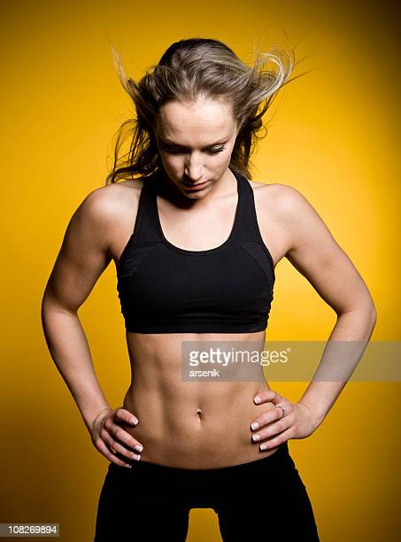 Young Muscular Woman in Exercise Clothing, Isolated on Yellow