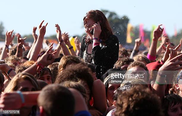 A young music fan gets water thrown in her face as she talks on the phone at the Main stage during the third and final day of Reading Festival on...