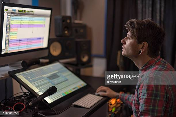 Young music producer working on computer in recording studio.