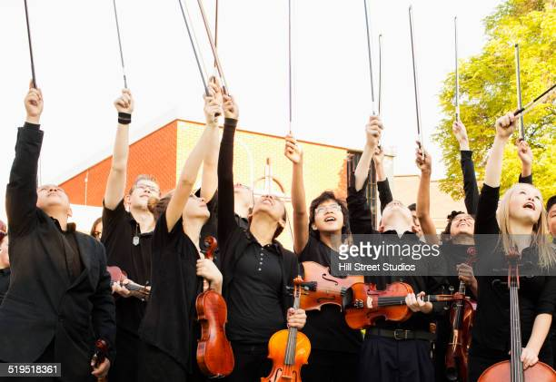Young musicians cheering with instruments