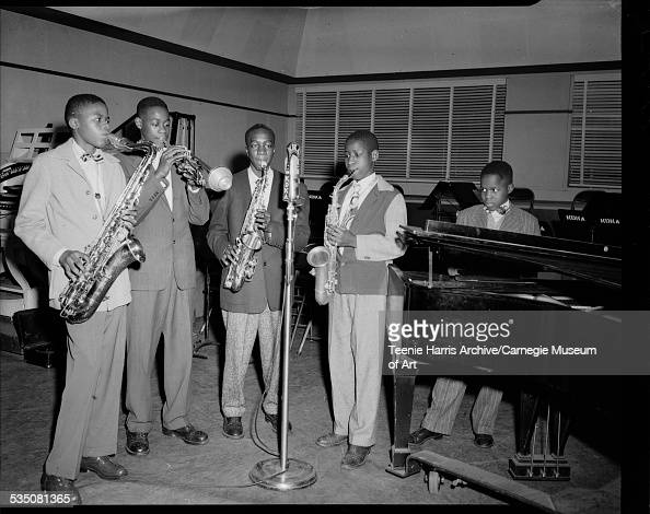 Young musicians including Stanley Turrentine on saxophone Tommy Turrentine on trumpet Willie Love on saxophone unknown on saxophone and unknown piano...