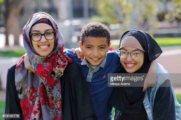 A young Muslim American mother and her two children, smiling at the camera in the park.