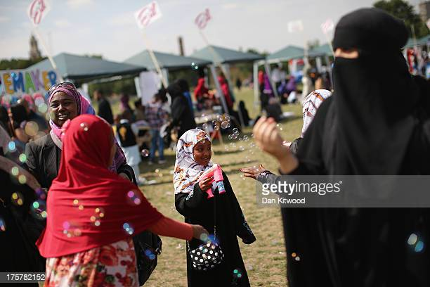A young muslim girl blows bubbles at an Eid celebration fun fair in Burgess Park on August 8 2013 in London England The Muslim holiday Eid marks the...
