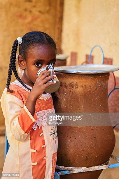 Young Muslim girl drinking water from well in Southern Egypt