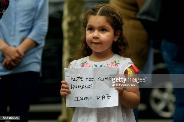 A young Muslim girl holds a message reading 'First of all we are human Islam is peace' as Muslim residents of Barcelona demonstrate on the Las...