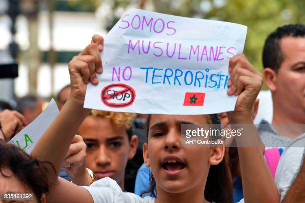 A young muslim girl holds a message reading 'We are muslims not terrorists' as Muslim residents of Barcelona demonstrate on the Las Ramblas boulevard...