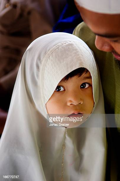 A young Muslim girl is dressed in traditional clothes for a wedding ceremony