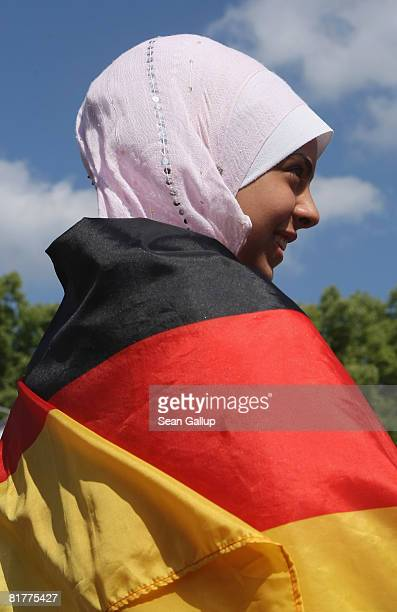 A young Muslim girl wearing a headscarve and a German flag waits for the German national football team to arrive at the Fan Mile in front of the...
