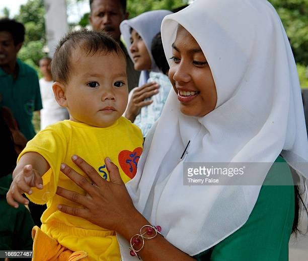 A young Muslim woman carrying a baby with a tshirt bearing the words 'We love the King' in one of the three Muslim majority provinces in Southern...
