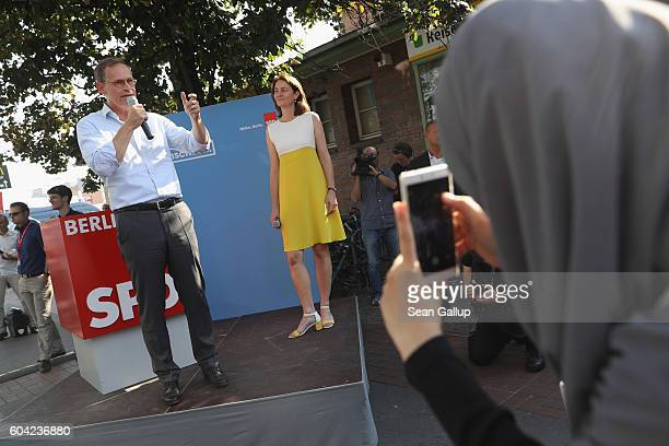 A young Muslim woman films German Social Democrat and current Berlin Mayor Michael Mueller speak as he campaigns in Berlin state elections outside...