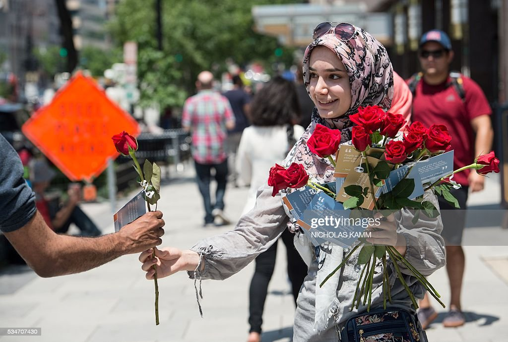 A young Muslim woman hands out roses during an operation called 'A Rose for Peace' in Washington, DC, on May 27, 2016. / AFP / Nicholas Kamm