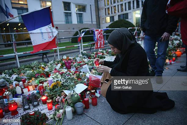 A young Muslim woman lights a candle outside the French Embassy among candles messages and flowers left by mourners commemorating the victims of last...