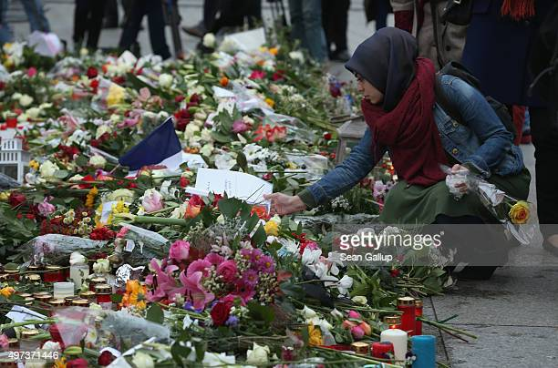 A young Muslim woman reads a message outside the French Embassy among candles messages and flowers left by mourners commemorating the victims of last...