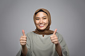 young muslim woman smiling at camera and showing thumb up isolated on grey