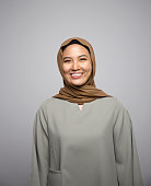young muslim woman smiling at camera isolated on grey