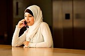 Young Muslim woman talking on cellphone.