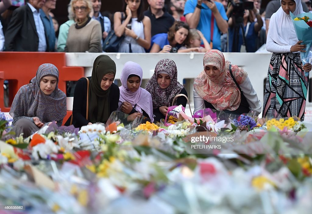 Young Muslim women lay flowers at a makeshift memorial near the scene of a fatal siege in the heart of Sydney's financial district on December 16...