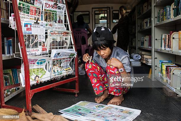 A young Myanmar girl reads the comic section of a newspaper at a mobile library on November 6 2015 in Kawhmu near Yangon Myanmar an impoverished...