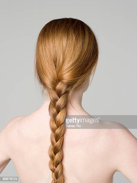 A young naked woman with a braided ponytail, rear view