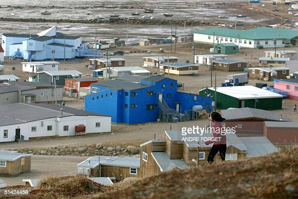 A young native girl runs on a hill overlooking the village of Iqaluit Nunavut Canada 05 October 2002 Britain's Queen Elizabeth II and her husband...