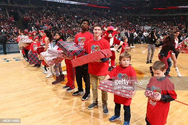 Young NBA fans receive gifts from players before the game between the Chicago Bulls and Los Angeles Lakers on December 25 2014 at the United Center...