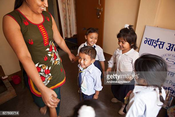 Young Nepalese children hold hands in a circle with a children's activity facilitator during a relationship building session facilitated by a staff...