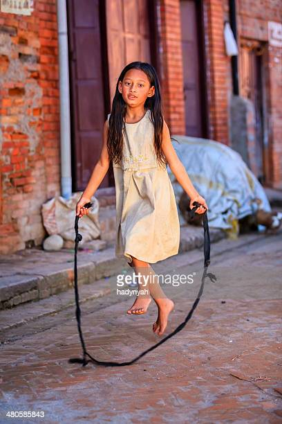 Young Nepalese girl having fun with jumping rope in Bhaktapur