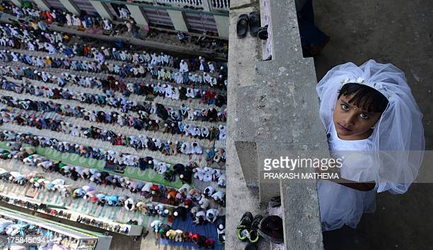 A young Nepalese Muslim child looks on as early morning Eid alFitr prayers are performed at Kashmiri Mosque in Kathmandu on August 9 2013 Muslims...