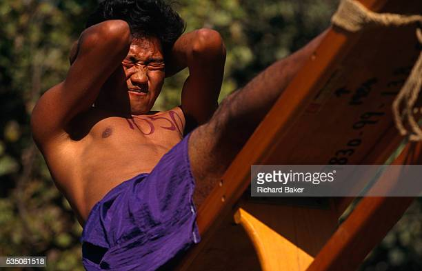 A young Nepali boy is straining in his last situps during a recruitment test for the Gurkha Regiment part of a tough endurance series to find...