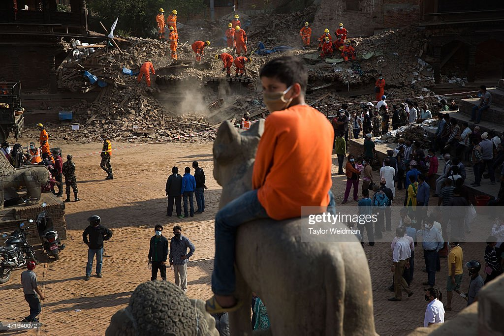 A young Nepali boy sits atop a carved statue and watches rescue teams clear rubble in Durbar Square in Bhaktapur Nepal on May 2 2015 On April 25...