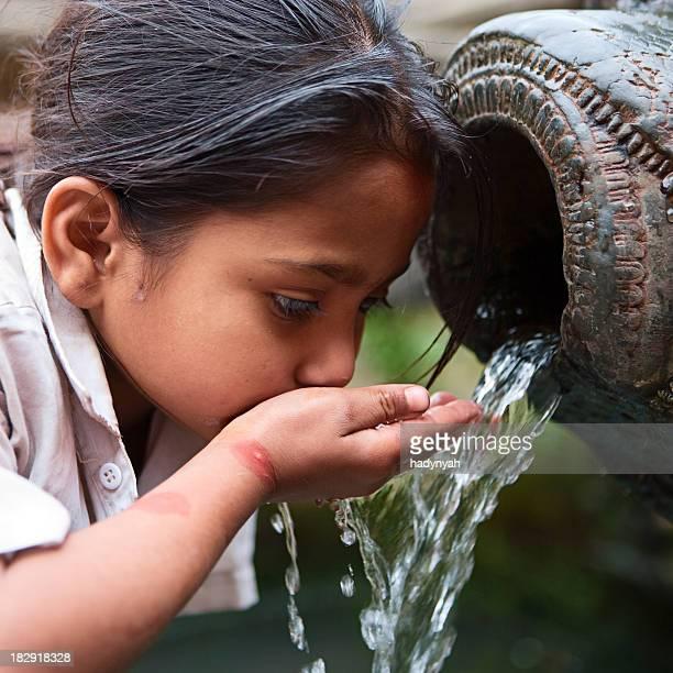 ネパールを飲む若い女性の都市であるダルバール広場の噴水