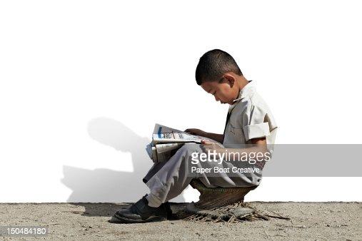 Young Nepali school boy reading newspaper