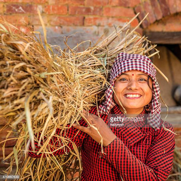 Young Nepali woman carrying a straw in Bhaktapur