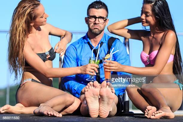 Young nerd sitting next to two beautiful women