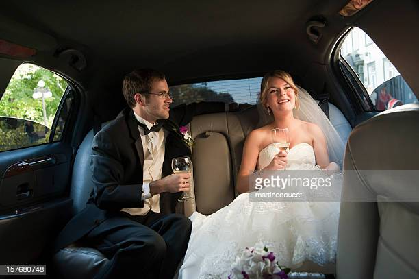 Young newlyweds drinking champagne in the limousine, horizontal